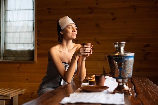 Giovane donna in una sauna con un berretto in testa si siede a un tavolo e beve una tisana, godendosi una giornata di benessere