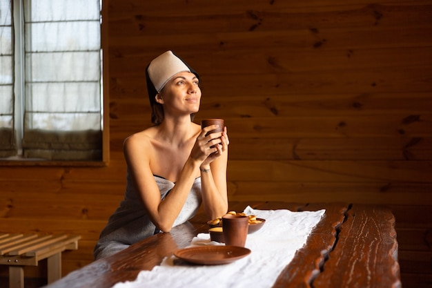 Young woman in a sauna with a cap on her head sits at a table and drinks herbal tea, enjoying a wellness day