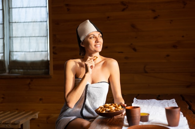 Young woman in the sauna with a cap on her head sits at a table with round bagels, honey and tea enjoying a wellness day