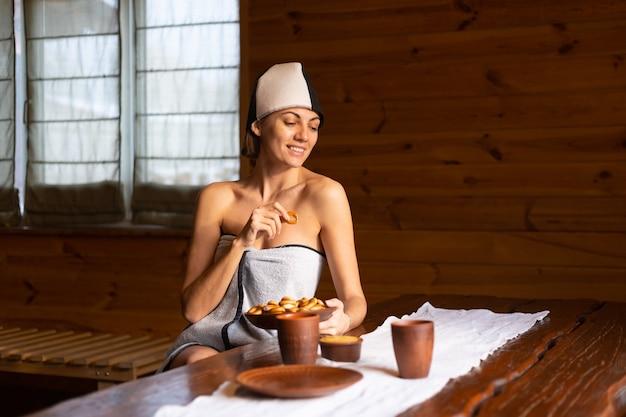 Giovane donna nella sauna con un berretto in testa si siede a un tavolo con ciambelle rotonde, miele e tè godendo di una giornata di benessere