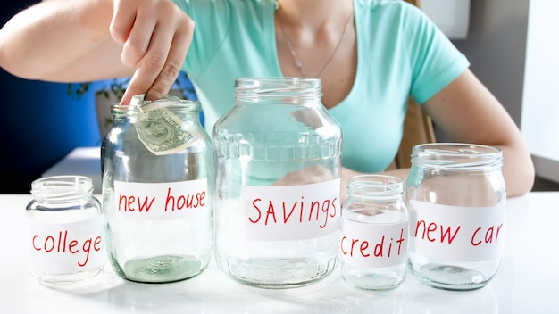 새 집을 사기 위해 돈을 절약하는 젊은 여자. 금융 투자, 경제 성장 및 은행 저축의 개념.