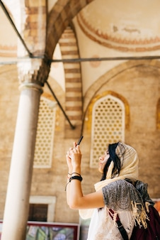 A young woman in a scarf takes pictures in the courtyard of the mosque on the phone