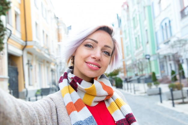 Young woman in a scarf takes a selfie against the background of the city