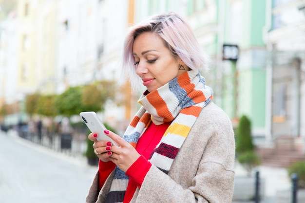 Young woman in a scarf with a mobile phone on a city
