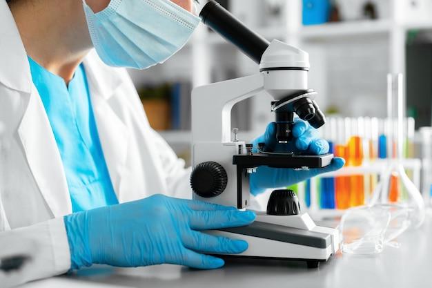 実験室で顕微鏡を使用して若い女性の科学者のクローズアップ