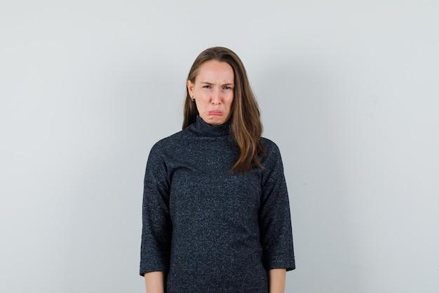 Молодая женщина хмурится, плачет в рубашке и выглядит обиженной. передний план.