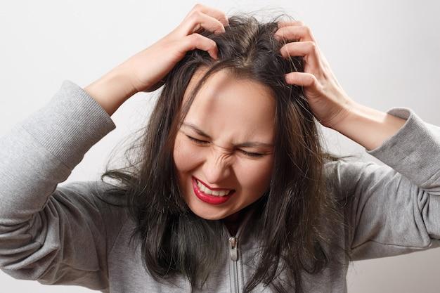 Молодая женщина чешет голову пальцами