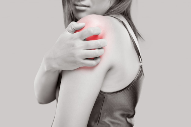 Young woman scratching arm from having itching on white.