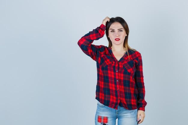 Giovane donna che graffia la testa in camicia a quadri, jeans e sguardo pensieroso, vista frontale.