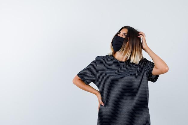 Молодая женщина почесывает голову, взявшись за талию в черном платье, черной маске и задумчиво, вид спереди.