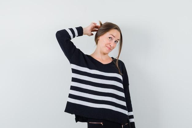 Молодая женщина почесывает голову в полосатом трикотажном белье и черных брюках и выглядит оптимистично