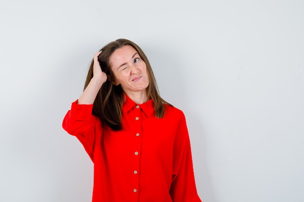 Young woman scratching head, looking up in red blouse and looking pensive , front view.