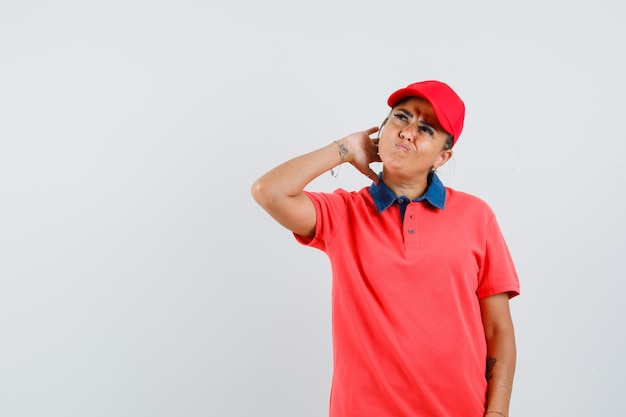 Молодая женщина почесывает голову, думая о чем-то в красной рубашке и кепке и задумчиво, вид спереди.