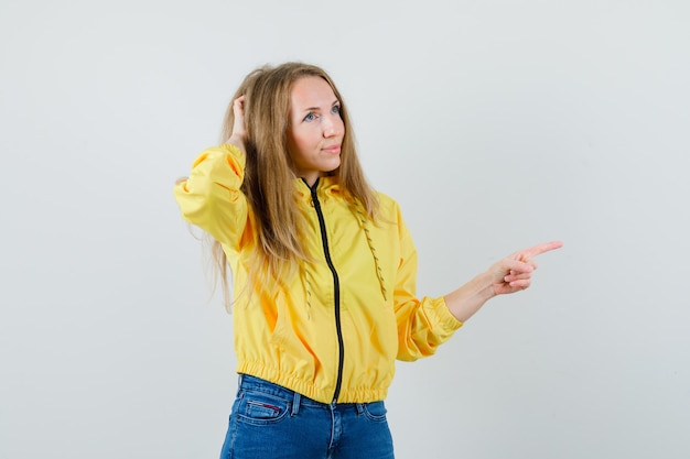 Молодая женщина почесывает голову, указывая вправо в желтой куртке-бомбардировщике и голубых джинсах и смотрит задумчиво, вид спереди.