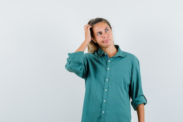 Young woman scratching head while thinking about something in green blouse and looking pensive