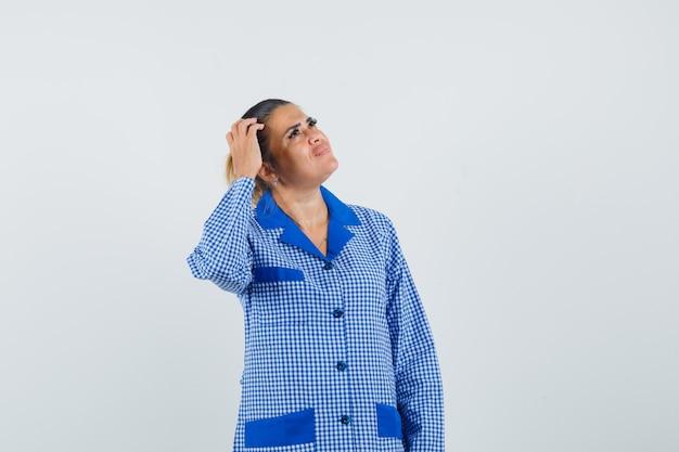 파란색 깅엄 파자마 셔츠에 뭔가에 대해 생각하고 잠겨있는 찾고있는 동안 머리를 긁적 젊은 여자. 전면보기.