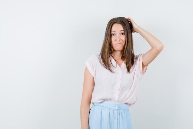 Tシャツ、スカート、躊躇しているように考えながら頭を掻く若い女性、正面図。