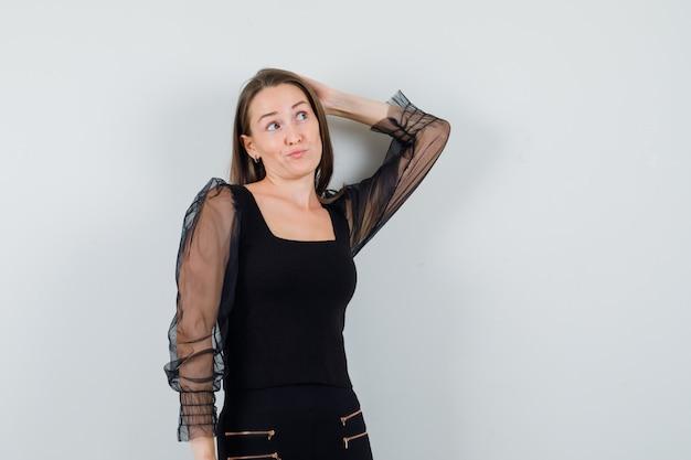Giovane donna grattandosi la testa con una mano, pensando a qualcosa in camicetta nera e pantaloni neri e guardando pensieroso, vista frontale.