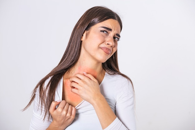 Young woman scratching her neck due to itching on a gray background. female has an itching neck. the concept of allergy symptoms and healthcare