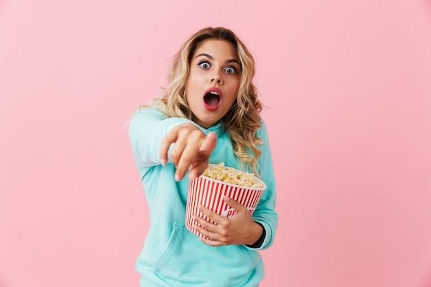 Молодая женщина кричит и держит ведро с попкорном, изолированное над розовой стеной