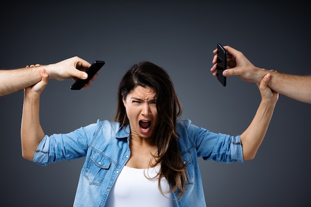 Young woman screaming and holding hands with phones because she don't want any phones in her life.