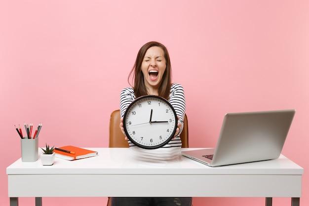 Молодая женщина кричала, держа круглый будильник, сидя, работая за белым столом с портативным компьютером