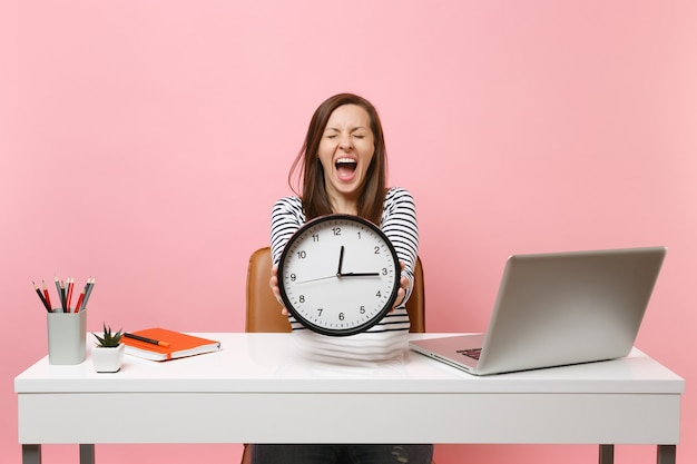 Young woman screaming holding round alarm clock while sit, work at white desk with pc laptop