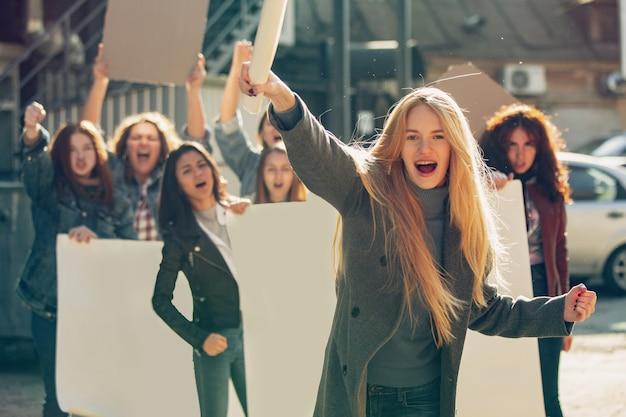 路上で女性の権利と平等に抗議する人々の前で叫ぶ若い女性。職場の問題、男性のプレッシャー、家庭内暴力、ハラスメントについてのミーティング。コピースペース。