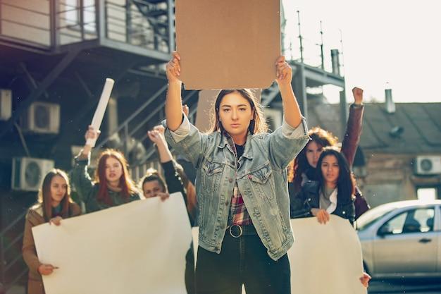 여성의 권리와 평등에 대해 항의하는 사람들 앞에서 비명을 지르는 젊은 여성