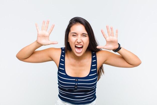 頭の横に手を置いて、パニックや怒り、ショック、恐怖、激怒で叫んでいる若い女性
