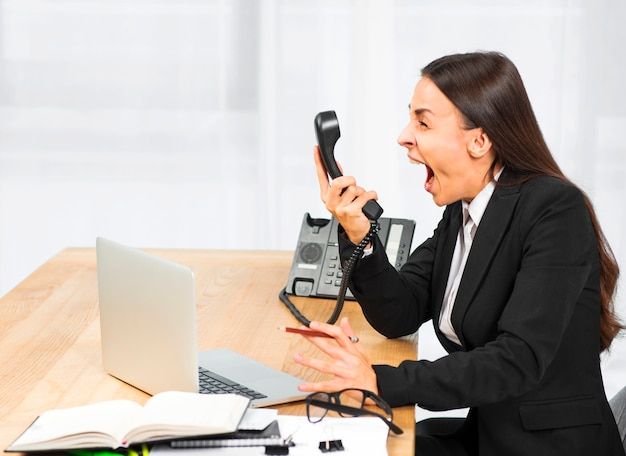 Young woman screaming on telephone at workplace