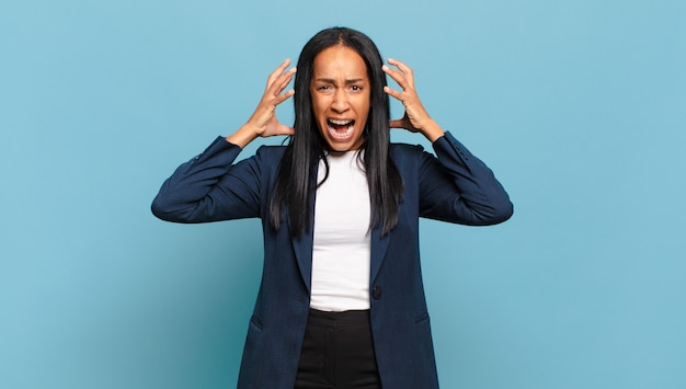 Young woman screaming with hands up in the air, feeling furious, frustrated, stressed and upset