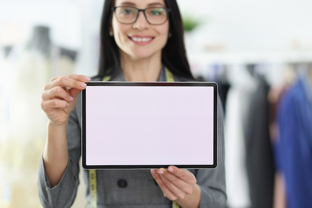 Young woman seamstress holding digital tablet in her hands closeup. online orders concept