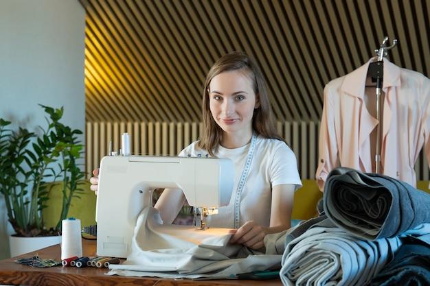 젊은 여자 재봉사는 테이블에 앉아 재봉틀에 바느질