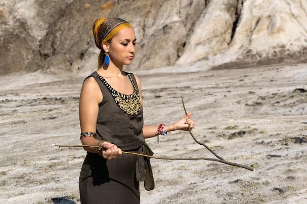 젊은 여성이 수맥을 통해 사막 지역에서 물을 찾습니다.
