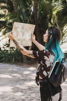 Young woman searching direction in the map