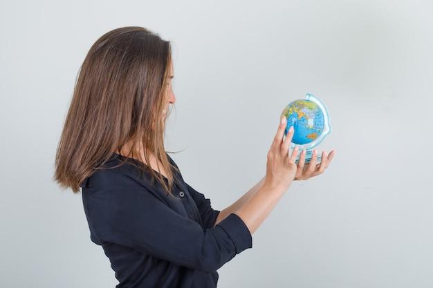 Молодая женщина ищет место назначения на земном шаре в черной рубашке и выглядит веселой.