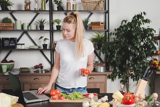 Молодая женщина, поиск рецепт на ноутбуке на кухне