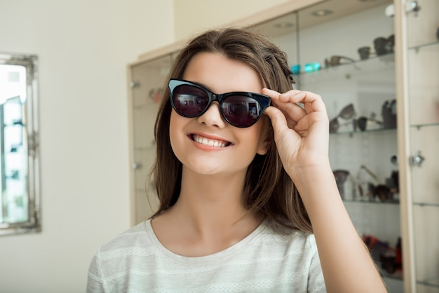 Young woman seeks new sunglasses to accent her style indoor