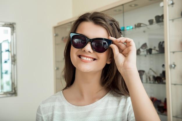 若い女性は彼女のスタイルを強調するために新しいサングラスを求めていますインドア