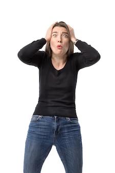 若い女性はショックと欲求不満の表情で彼女の頭を手につかみます。