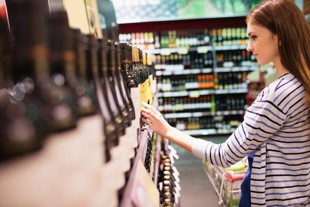 Молодая женщина, выбирая вино