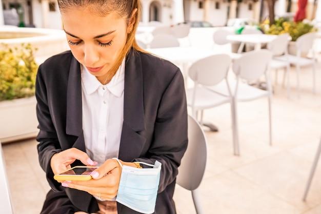 保護フェイスマスクを手に持ってバーdehorsに座っているスマートフォンで若い女性の自己起業家のテキストメッセージ。テクノロジーを使ってホテルのカフェで朝食をとるフリーランスの女の子。新しい通常の習慣