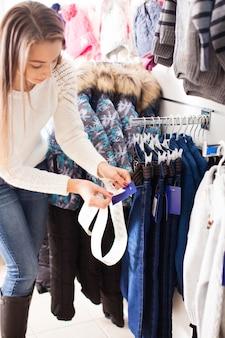 Девушка-продавец склеивает цены на товар - детская одежда
