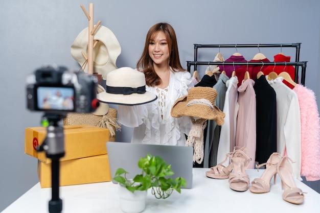 카메라 라이브 스트리밍으로 모자와 옷을 온라인으로 판매하는 젊은 여성, 집에서 비즈니스 온라인 전자 상거래