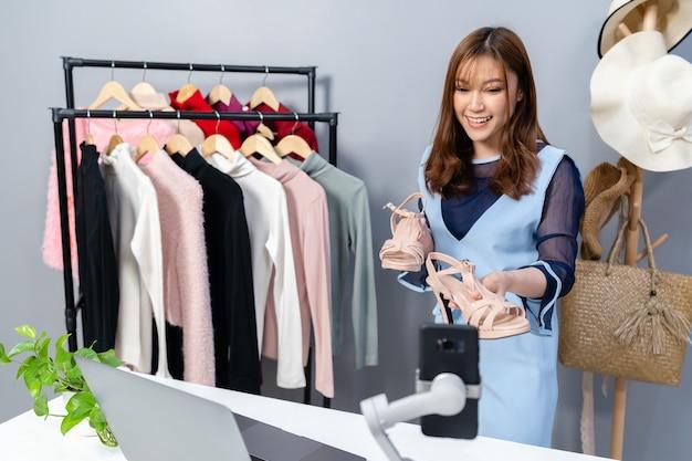 スマートフォンのライブストリーミング、自宅でのビジネスオンラインeコマースによって靴や服をオンラインで販売する若い女性