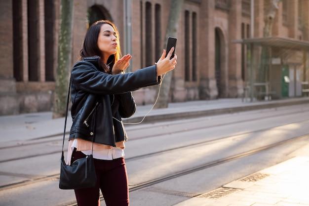 Молодая женщина отправляет поцелуй, делая видеозвонок