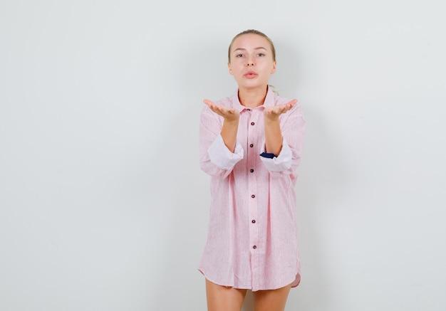 ピンクのシャツでエアキスを送信する若い女性
