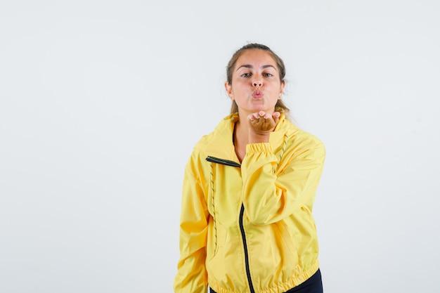 Giovane donna che invia un bacio d'aria in impermeabile giallo e sembra adorabile