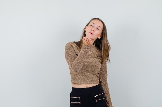 Giovane donna che manda baci davanti in maglione dorato e pantaloni neri e sembra felice